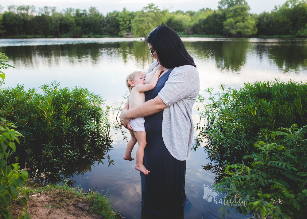 young woman standing in a lake breastfeeding her baby