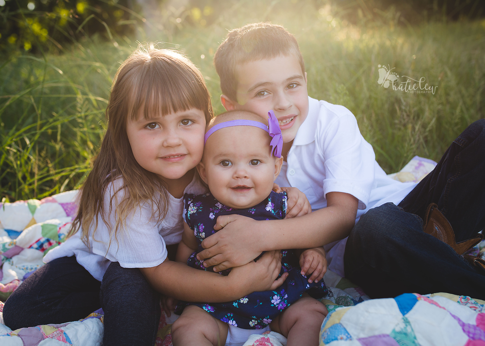 6 month old baby girl with her older brother and sister for their sibling pictures
