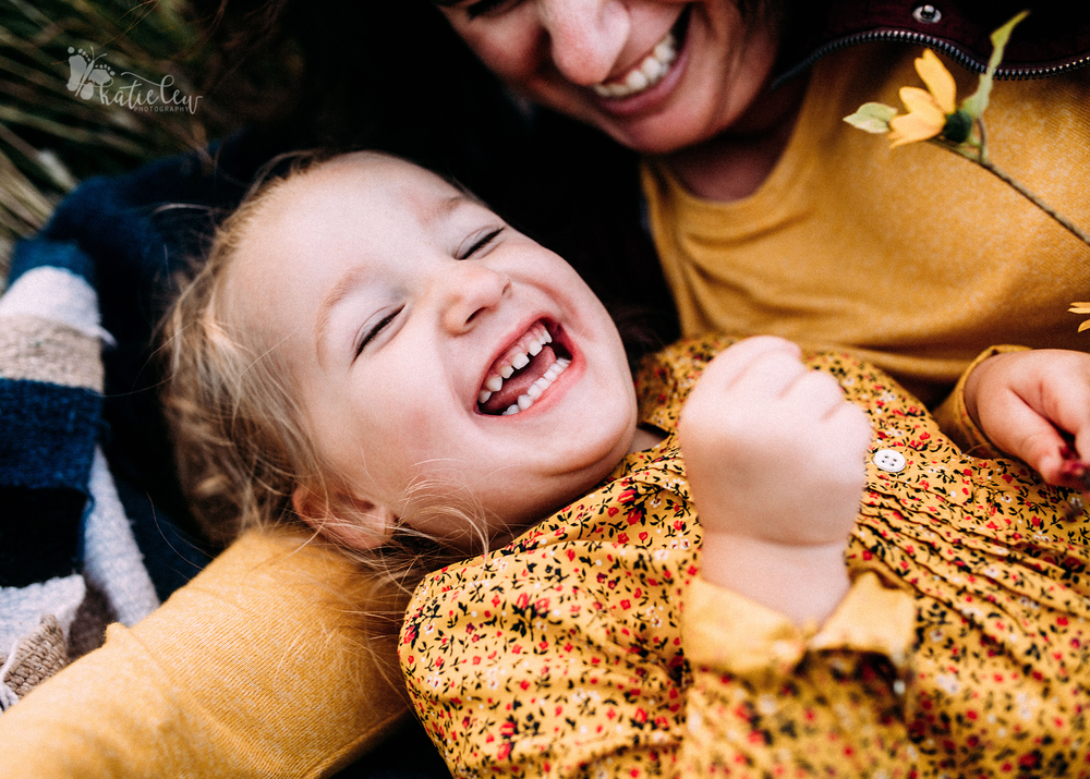 smiling, happy girl being cuddled by her mother in their family pictures