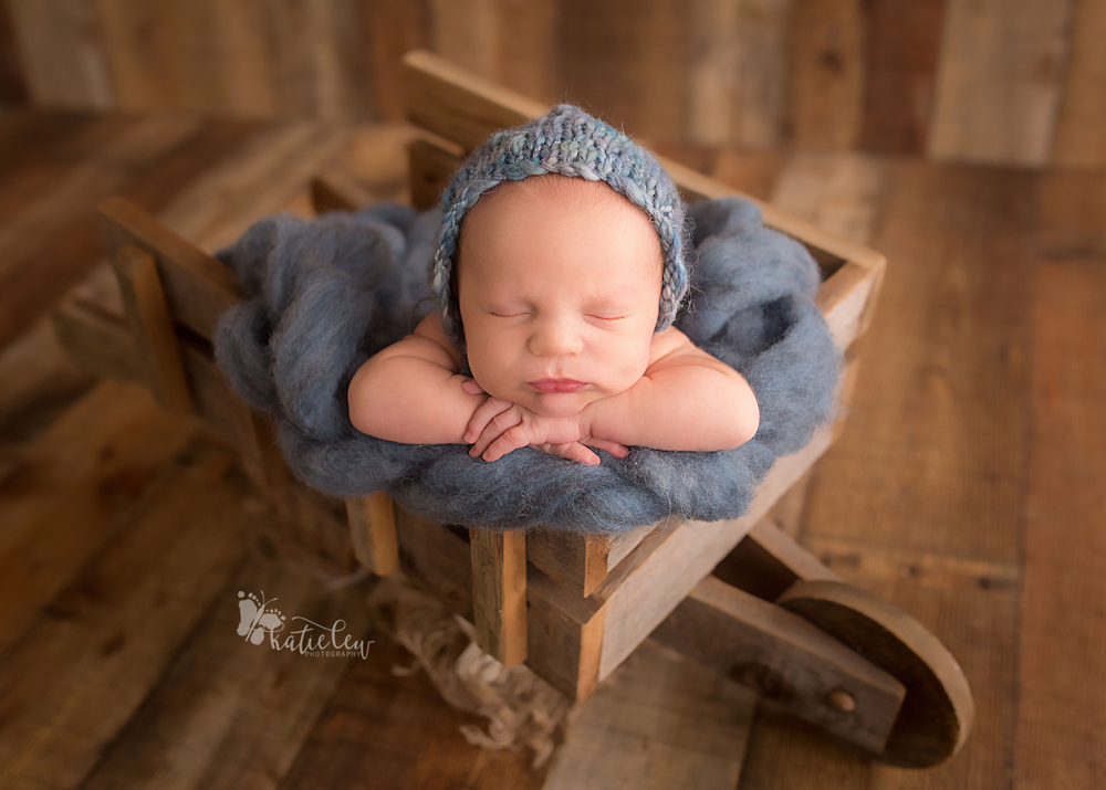 newborn baby boy wearing a blue bonnet and sitting in a wheel barrow