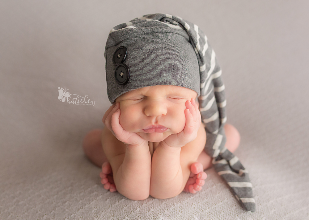 newborn baby boy wearing a striped hat