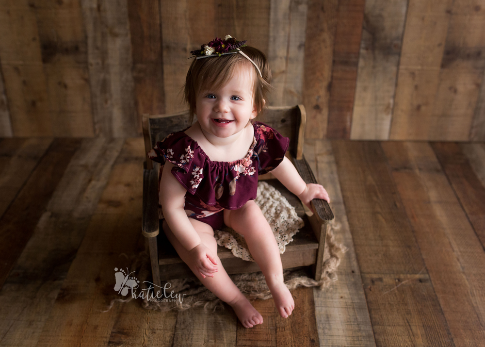 Young 9 month sitter girl wearing cute floral romper