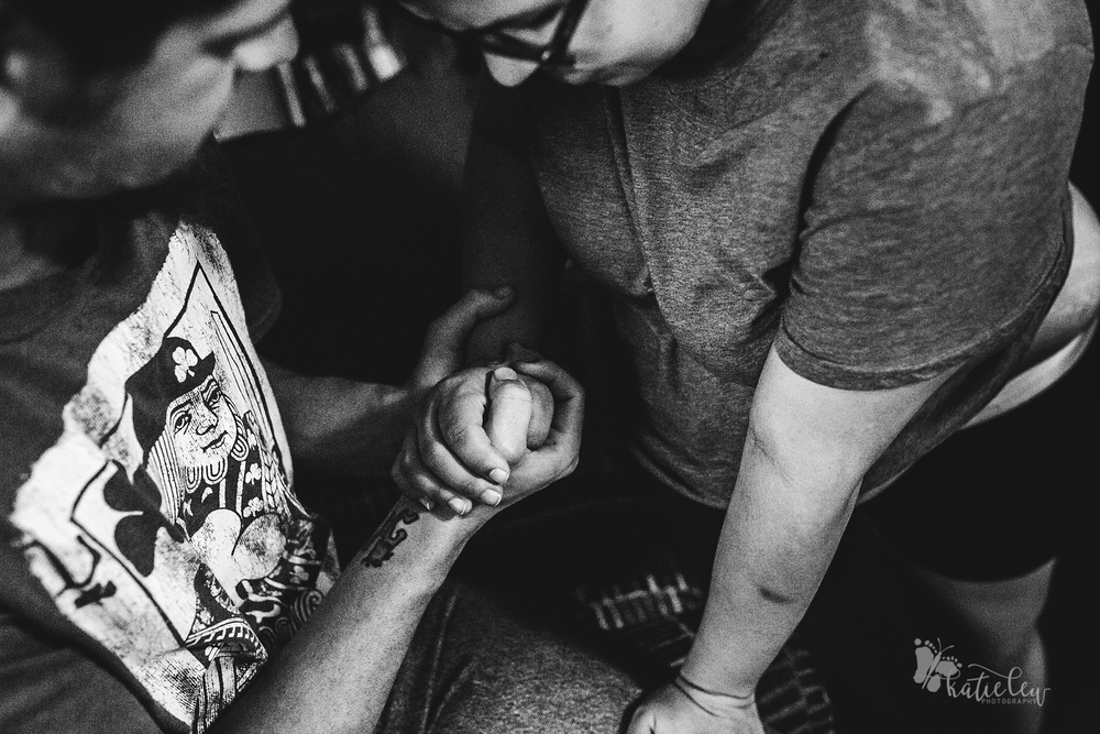 laboring woman grips her partners hand through contraction