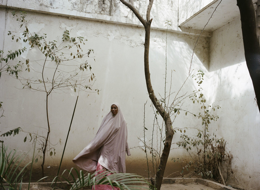 """Rabi Talle in the courtyard of her office in the Ministry of Information in Kano, Northern Nigeria. Her next book is called """"Victim of Love."""" Photo by Glenna Gordon"""