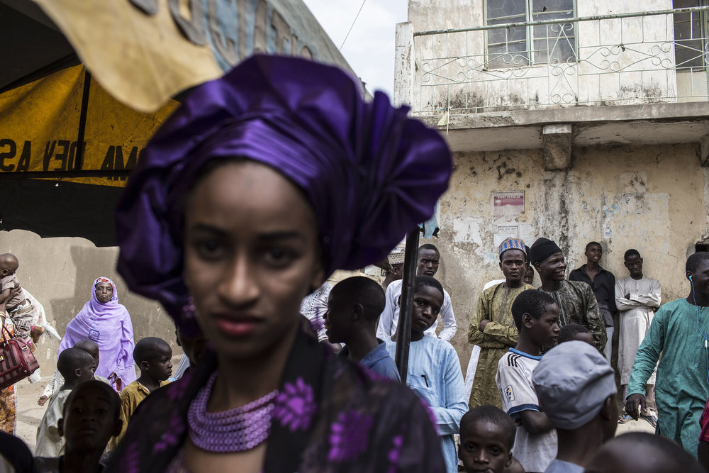 A bride at a wedding in Kano, Northern Nigeria, stands apart from the guests. Male guests and female guests seldom mix in the conservative Islamic norther part of Nigeria. Photo by Glenna Gordon