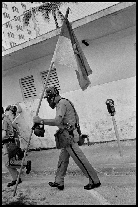 A policeman carrying a confiscated Vietcong flag while wearing a gas mask during an anti-war protest at the Republican Convention. Photographed by Abbas/Magnum.