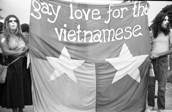 "Demonstrators holding a ""Gay Love for the Vietnamese"" sign at an anti-war rally during the GOP Convention. Photographed by John Buckley."
