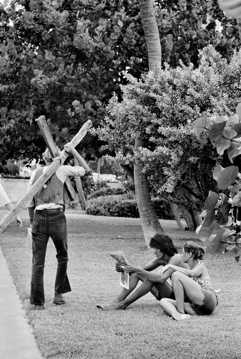 An evangelist carrying his cross in a park where a young hippie couple relaxes on the grass outside the Republican Convention. Photographed by Abbas/Magnum.