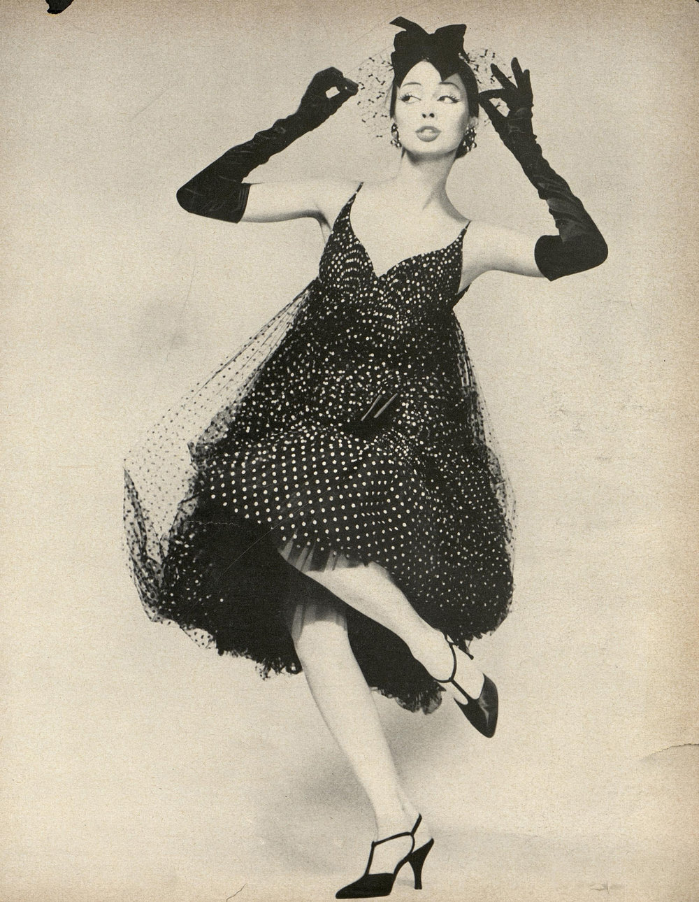 """This enchantment is made of coppery-dotted black point d'esprit, billowed from a point just below the bosom into a great, blown skirt that's caught above the knee with a satin bow, then released into a deep flounce."" Photographed by Richard Avedon for Harper's Bazaar, February 1958."