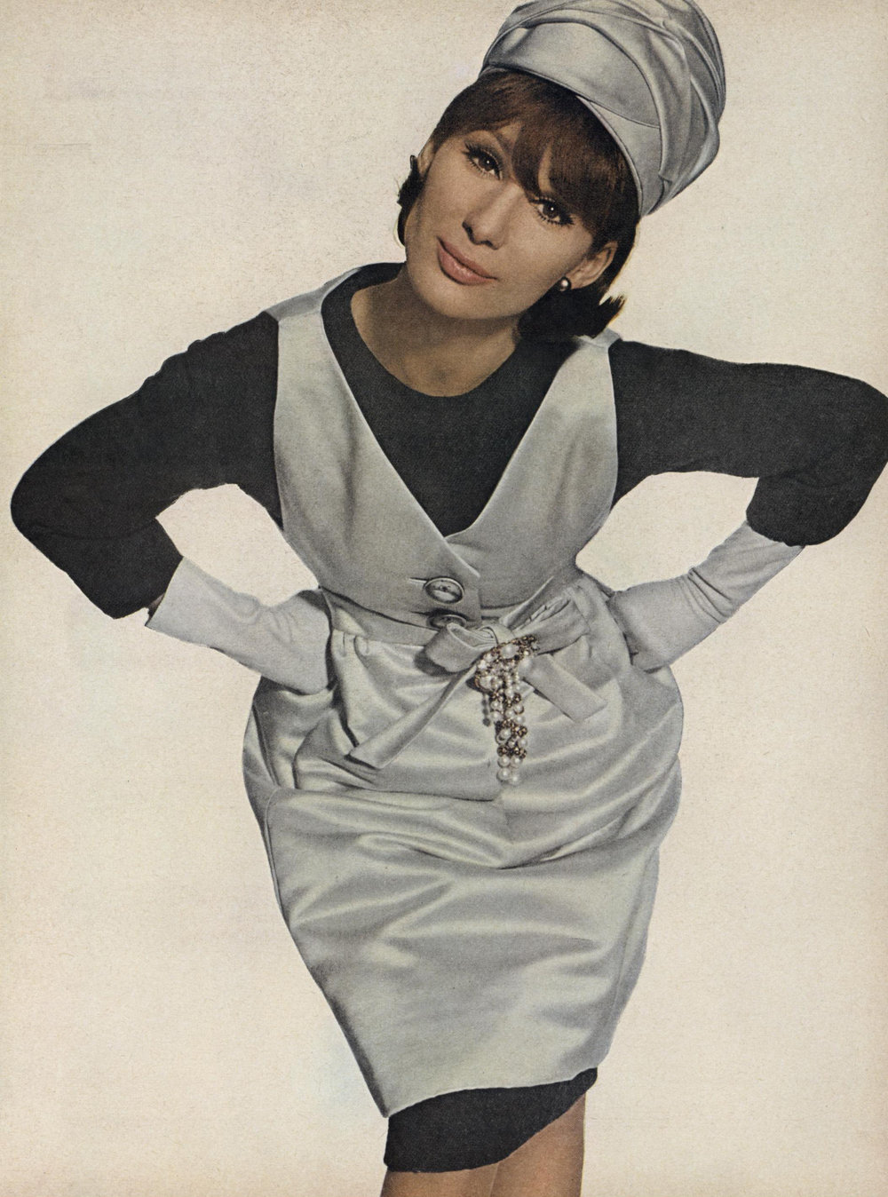 A pale-grey satin tunic worn as a pinafore over a simple dark grey wool sheath, with matching turban. Photographed by Irving Penn for  Vogue,  July 1963.