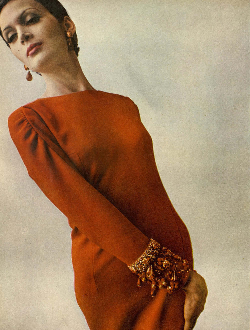 """Serene line, Baroque ornamentation"": A burnt orange wool dinner dress with beaded cuffs. Photographed by James Moore for Harper's Bazaar, November 1963."