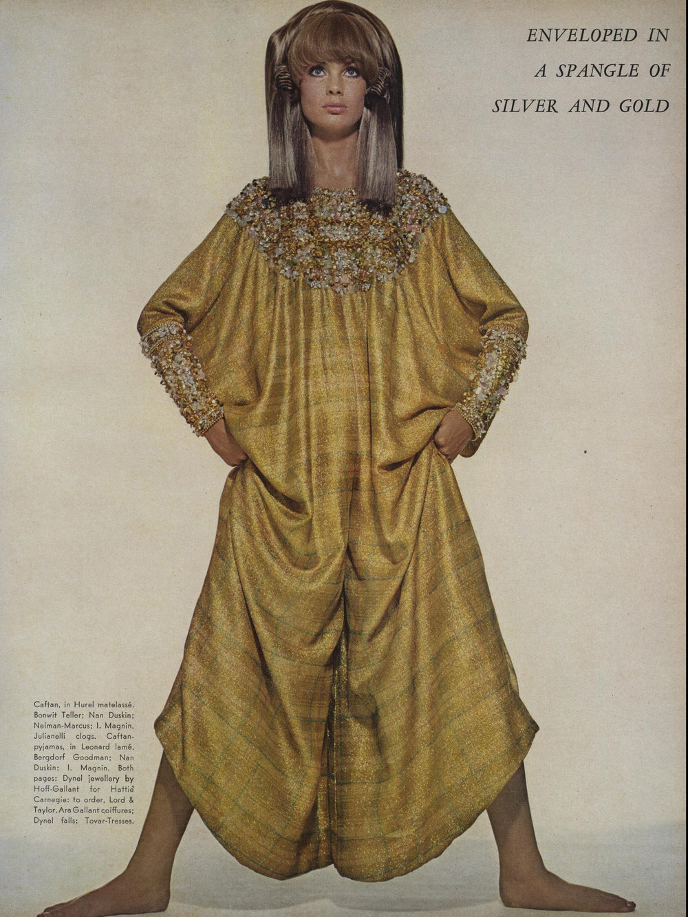 Jean Shrimpton in a gold lamé caftan jumpsuit, heavily embroidered with opalescent stones on the yoke and cuffs. Photographed by Richard Avedon for  Vogue , November 1966.