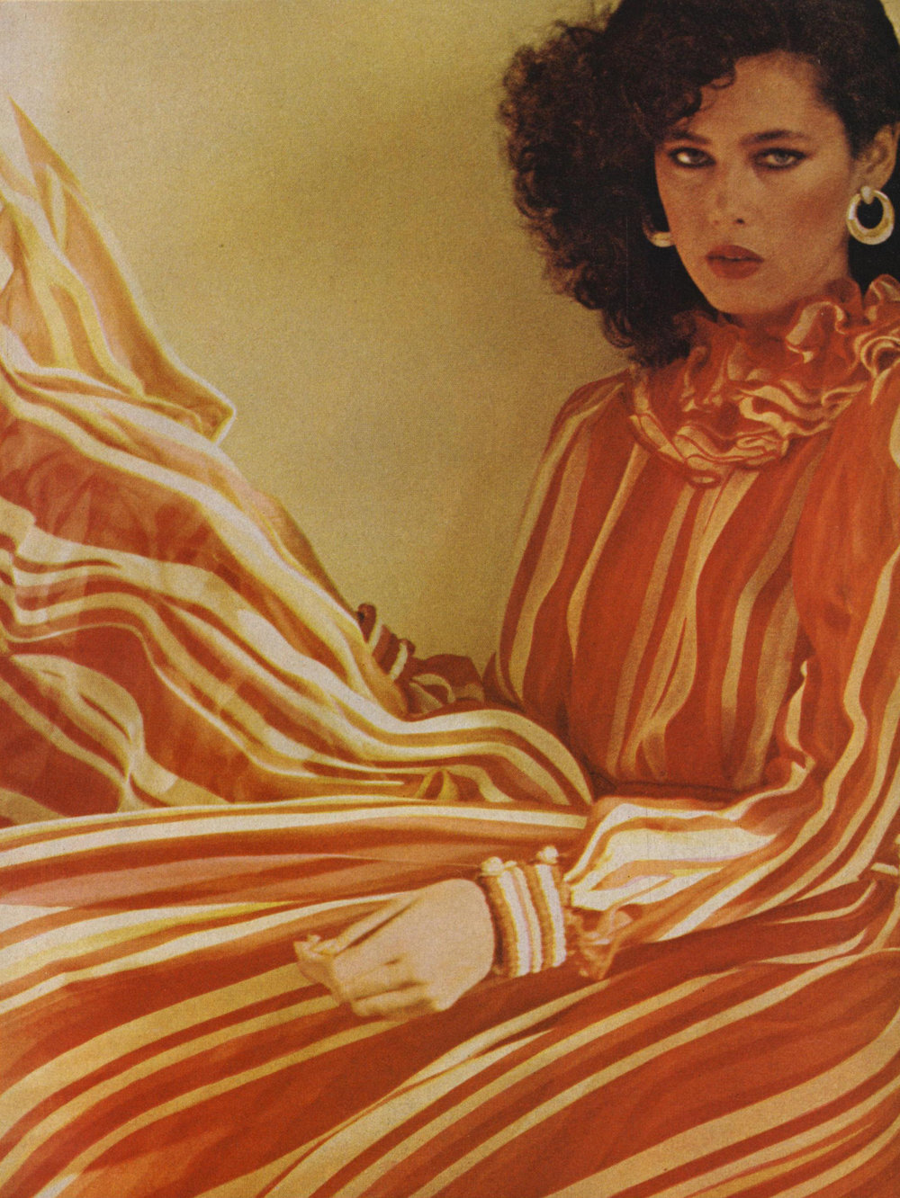 Galanos made his name in the early '50s due to his skilled use of chiffon, and continued to excel at it throughout his career. In 1977—the same year as his first retrospective exhibition, at the Fashion Institute of Technology—Jimmy paired a Pierrot collar with stripes of flame-and-white chiffon. Photographed by Arthur Elgort for  Vogue , June 1977.