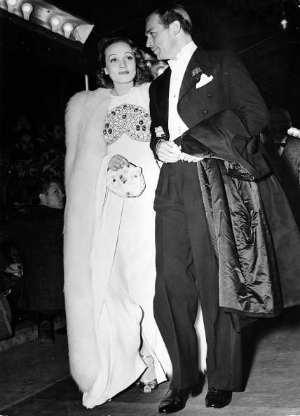 Marlene Dietrich, in white crêpe and fox, arriving at a film premiere with Douglas Fairbanks Jr. in Hollywood, 1937.