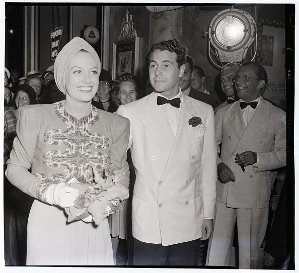 Joan Crawford, in a heavily embroidered jacket and turban, accompanied by Charles Martin to the premiere of  The Old Maid  at the Beverly Hills Theater on July 30, 1939.