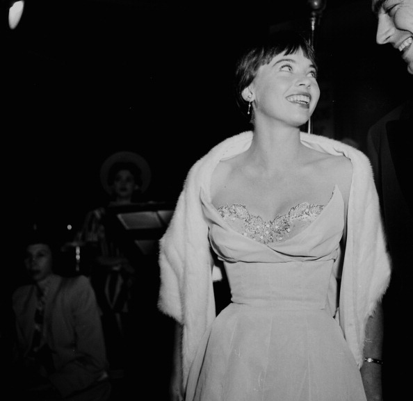 Leslie Caron, in a strapless taffeta dress and fur stole, at the premiere of  An American in Paris  in Los Angeles.