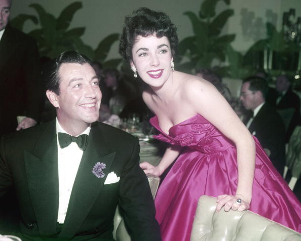 In strapless magenta satin, Elizabeth Taylor talks with Robert at the premiere after-party for  Quo Vadis  in Los Angeles on 29th November 1951.