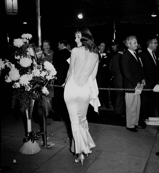 Wearing one of the scandalously low-backed dresses she was infamous for, Vikki Dougan attending the premier of  Heaven Knows, Mr. Allison  in Los Angeles, March 15th, 1957.