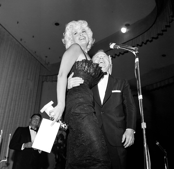 In skintight lace, Jayne Mansfield accepting her Golden Globe award from actor Mickey Rooney for 'New Star Of The Year' in Los Angeles on February 22, 1958.