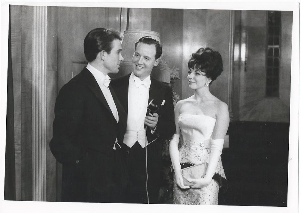 Joan Collins, in an embroidered white column and opera gloves, chatting with Nicholas Parsons and boyfriend Warren Beatty at the London premiere of  The Roman Spring of Mrs Stone  in 1961.