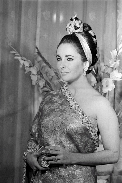 In Paris for a premiere on December 2, 1964, Elizabeth Taylor wears a gold sari by Balenciaga with an elaborate hairstyle by Alexandre.