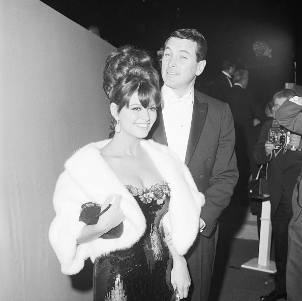 With a beehive and fully sequined strapless gown, Claudia Cardinale attends the Academy Awards with Rock Hudson on April 7, 1965.