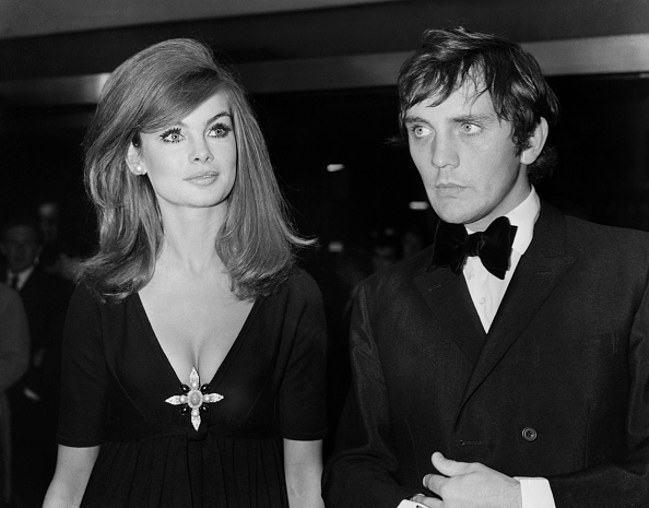 Jean Shrimpton, clad in a simple black dress amped up by lots of lashes and a large brooch, accompanies then-boyfriend Terence Stamp to a London premiere on October 14, 1965.