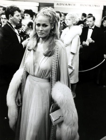 A deep plunge—major hair—fox trim. Perfect Ursula Andress arriving at the London premiere of  The Blue Max,  on July 1, 1966.