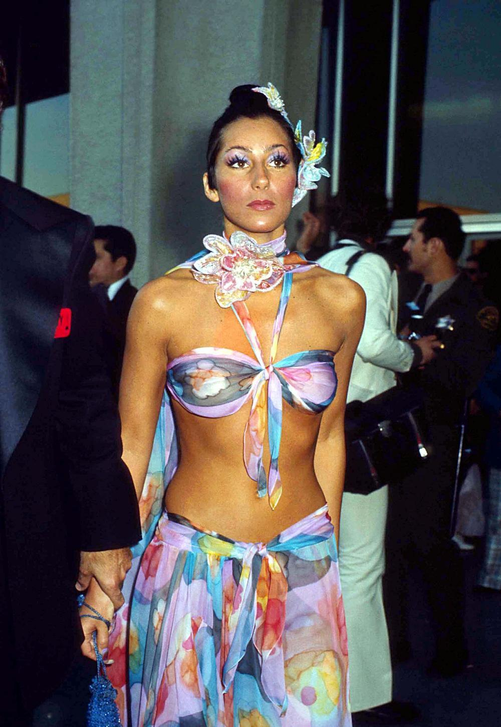 Only Cher could make a tropical Bob Mackie bandeau top and sarong skirt (complete with iridescent flowers around her neck and on her head) look appropriate for the Academy Awards in 1974.