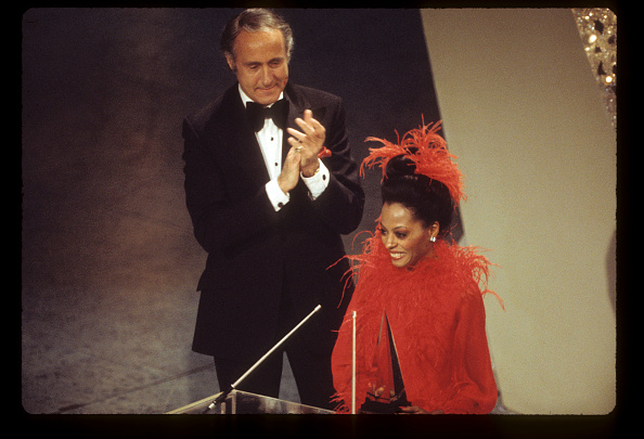Diana Ross, in red ostrich trimmed cape, accepting an award from Henry Mancini at the American Music Awards on February 19, 1974.