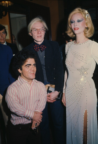In a sheer star-embellished dress, Monique Van Vooren attends the premiere party for the Broadway show 'Man on the Moon' with the show's producer, Andy Warhol, in January 1975.