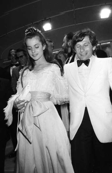Delicately pretty in organza ruffles, Nastassja Kinski attend a premiere at the Cannes Film Festival with Roman Polanski on May 19, 1979.