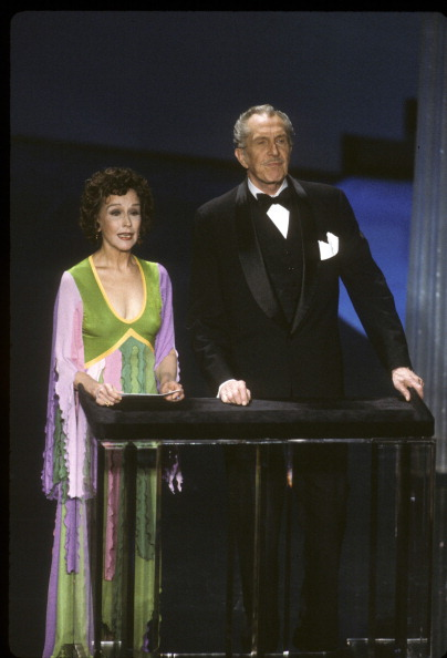 "Wearing a Giorgio di Sant'Angelo ribbon dress, Kim Hunter was a rainbow foil for Vincent Price when they presented the award for ""Best Makeup"" at the 54 th  Academy Awards on March 29, 1982."