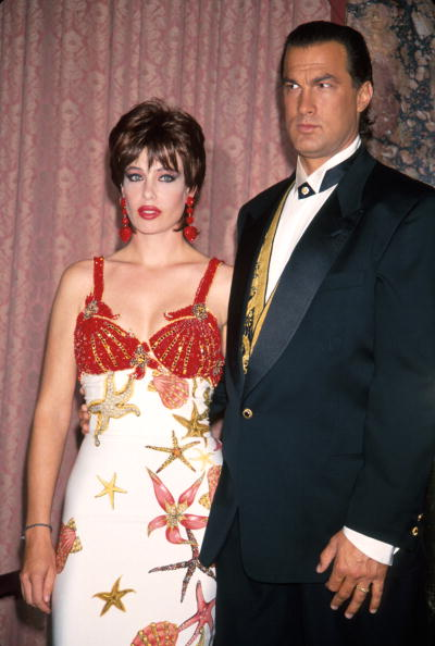 Versace Couture seashells and red lacquer lips make Kelly LeBrock (with husband Steven Seagal) the star of the National Hero Awards Gala Benefit Big Brothers and Big Sisters on October 26, 1992 at the Waldorf Astoria Hotel in New York.