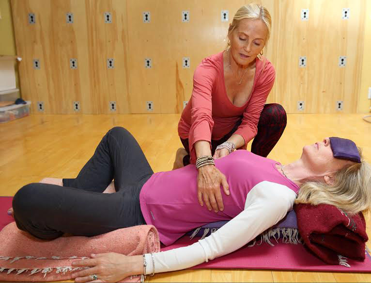 Ingrid helping a student into a restorative pose at Sacred Space, her yoga studio.