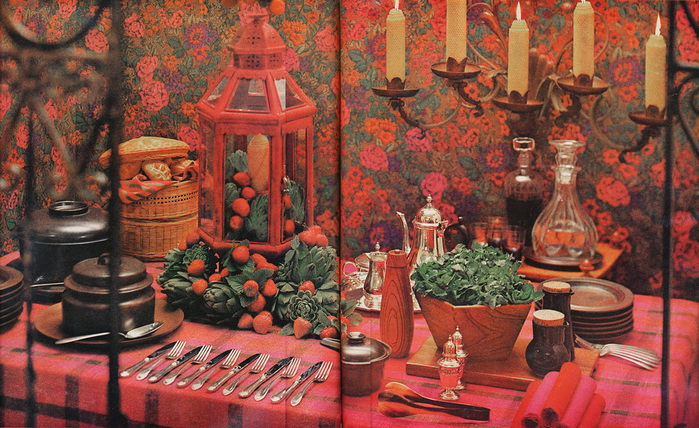 """Beauty queen in a national table-setting contest, this stunning table was judged 'best dressed.' Yes, despite its proud title, it is one that could be copied at no budget-breaking cost. The rosy colors of cloth and napkins are reflected in plump berries, massed among artichokes (use apples and eggplants in the fall), and the painted lantern. Wood-toned china, sparkling silver and crystal make an effective contrast."""