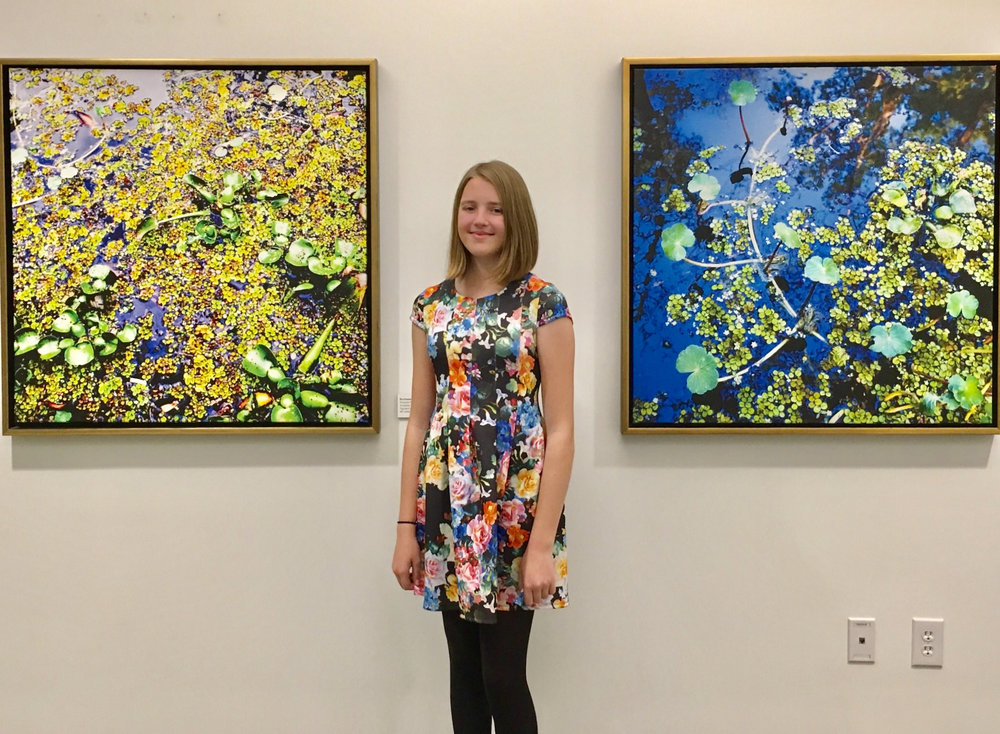 "Young environmentalist Isabelle Pierson at The Collider with (at left) Duckweed #1, 2008 (38"" x 38"" framed) and Duckweed #4, 2009 (38"" x 38"" framed),"