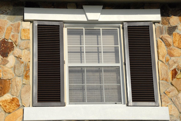 brown hurricane colonial shutters on a cobblestone house.jpg