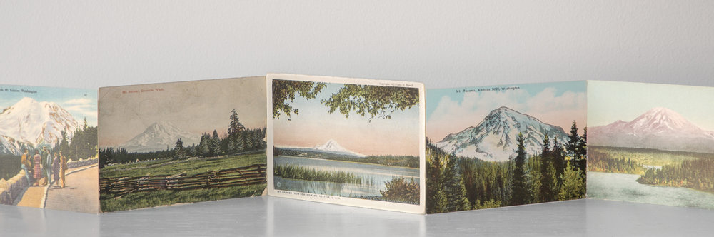 "Thirty-Six Views of Mt. Rainier #1   ,  2018 Vintage postcards, linen tape 189x3.25"" When my father and his family were sent to the Tule Lake incarceration center in 1942, they left behind a hillside home in Tacoma, WA, with a clear view of Mt. Rainier.  Thirty-six Views of Mr. Rainier #1  is the first of a series of works reflecting on place and visual memory while referencing Hokusai's series,  Thirty-six Views of Mt. Fuji."