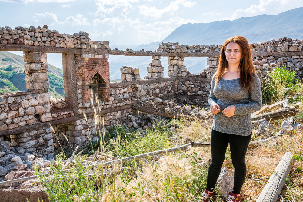 Nurcan Gündoğdu, inside the ruins of her family's home, which was destroyed by the Turkish military in 1994.