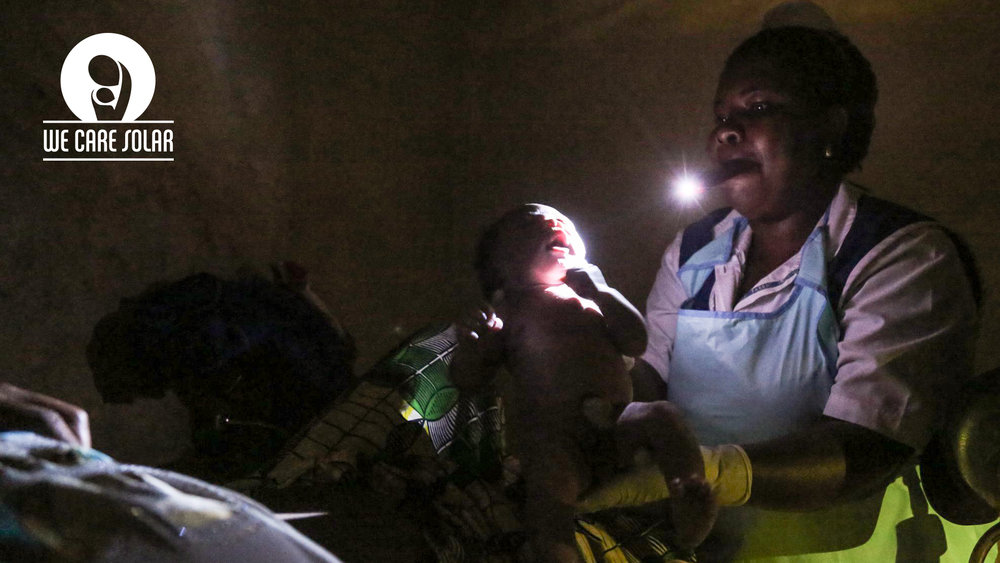 The health center without reliable lightning, trying to deliver a baby, and the only source of light is the cell phone midwife is holding in her mouth. Photo Credit:  Brian Emmanuel Inganga