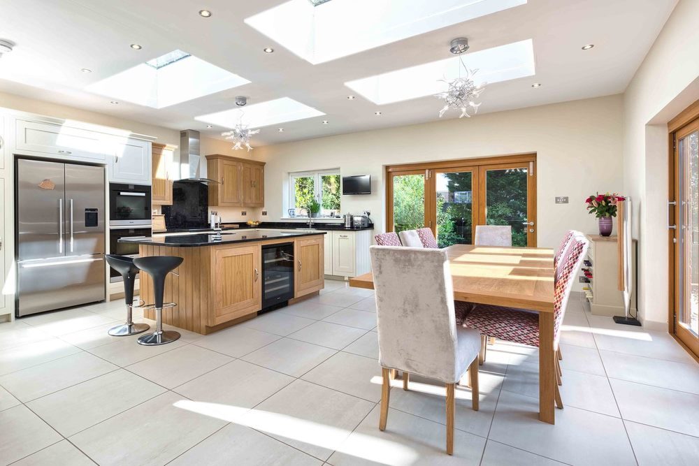 A dining room and kitchen with a skylight of a modern house extension by Harvey Norman Architects St Albans