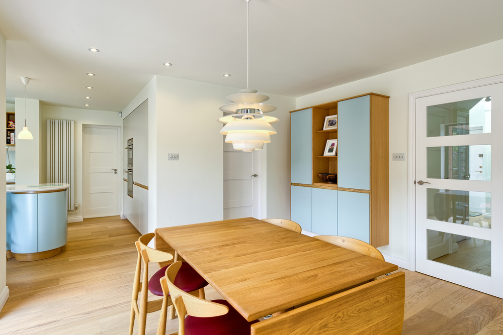 Wooden table and low hanging light of a Scandinavian house extension by Harvey Norman Architects Bishop's Stortford