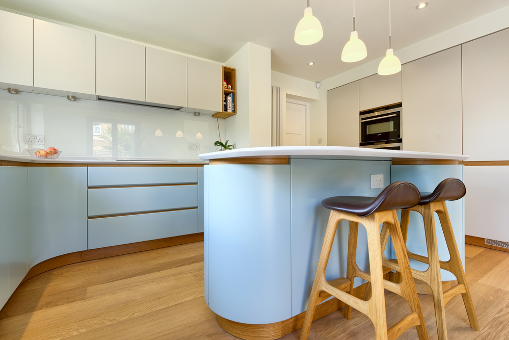 High stools for a breakfast bar of a Scandinavian house extension by Harvey Norman Architects Bishop's Stortford