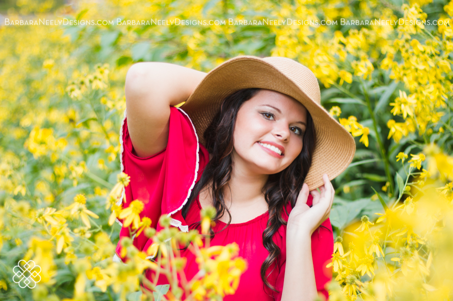 Senior girl wearing a hat in a field of flowers