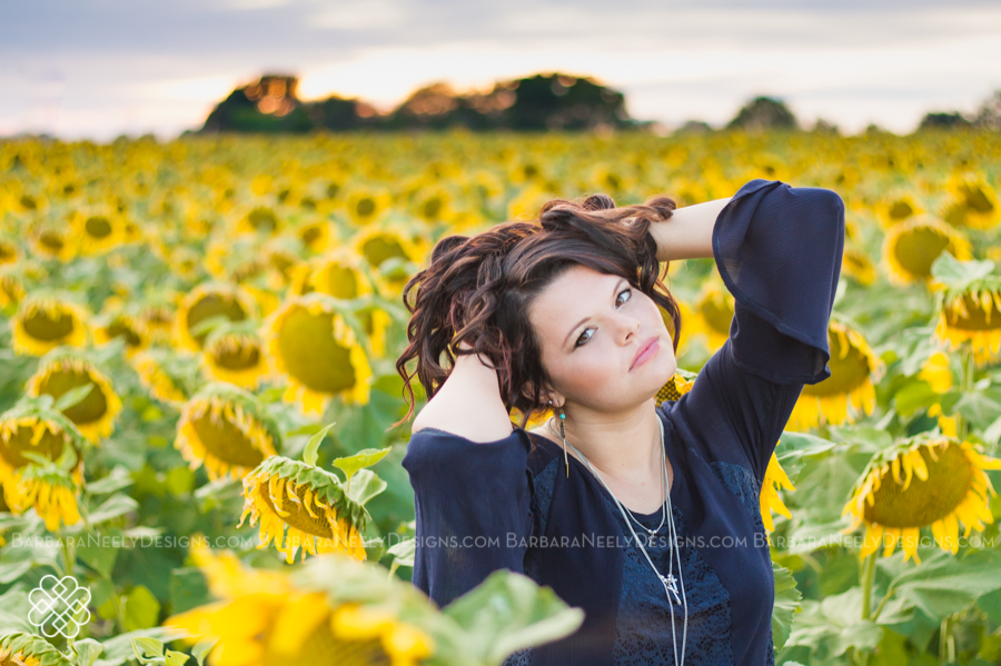 Gorgeous senior girl in sunflower field at sunset