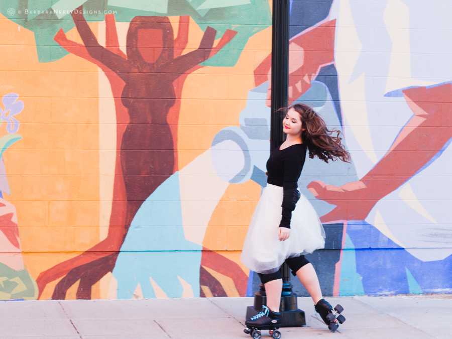 Vibrant senior girl in roller skates in front of mural