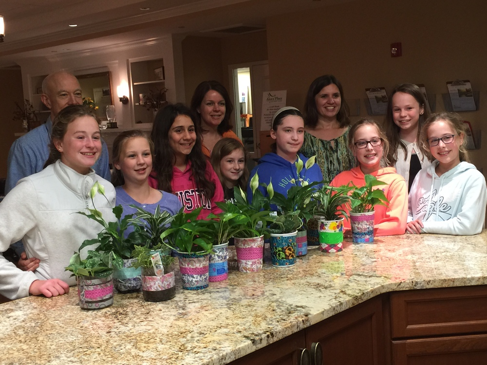 Members of Girl Scout Troop 50286 present purifying plants to Kevin Berrill, MSW, LCSW and Laura Donnelly, MSW, LCSW - Ann's Place
