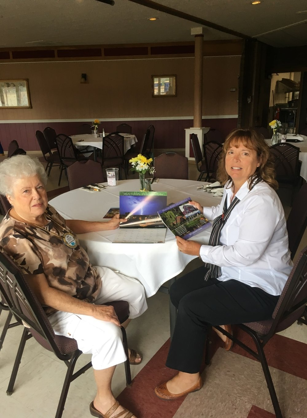 Nancy Kush Ellis, right, shows Judy Young some of the Fulton Savings Bank's calendars. Judy has collected each year's calendar since 1996.