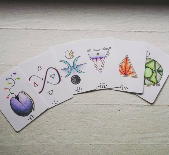 Here's the first five cards of a deck that I started to make for myself with just cardstock, colored pencils, metallic pens, and a corner-rounder!